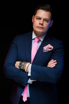 Portrait of confident handsome businessman with crossed arms on black