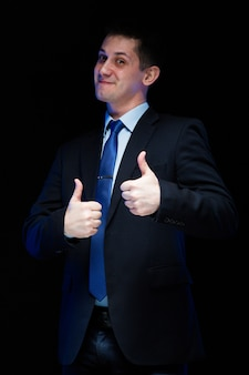 Portrait of confident handsome businessman with thumbs up on black background