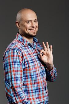 Ritratto dell'uomo allegro bello sicuro in camicia di plaid che sorride alla macchina fotografica che mostra gesto giusto sopra la parete grigia