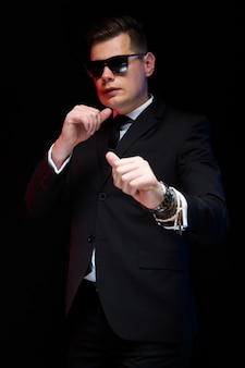 Portrait of confident handsome elegant businessman in sunglasses boxing