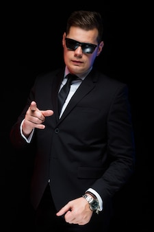 Portrait of confident handsome elegant businessman in sunglasses showing his power