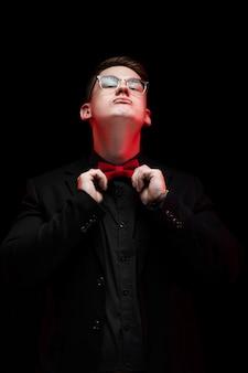 Portrait of confident handsome elegant responsible businessman correcting bow-tie