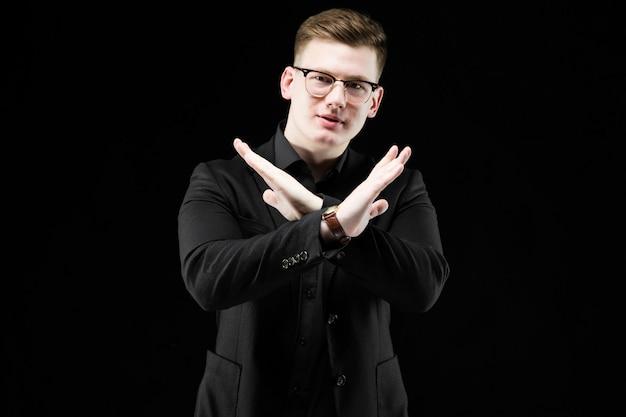 Portrait of confident handsome elegant responsible businessman showing stop gesture on black