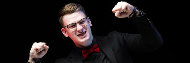 Portrait of confident handsome excited happy elegant responsible businessman showing fists as success concept on black background