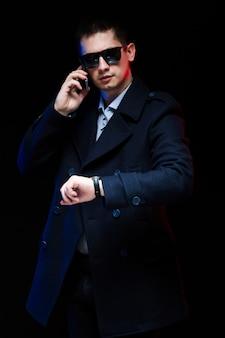 Portrait of confident handsome stylish businessman in black coat talking on phone