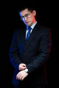 Portrait of confident handsome stylish businessman in glasses with hand on his suit on black background