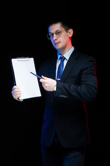 Portrait of confident handsome stylish businessman holding clipboard in his hands on black background