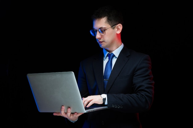 Portrait of confident handsome stylish businessman holding laptop in his hands