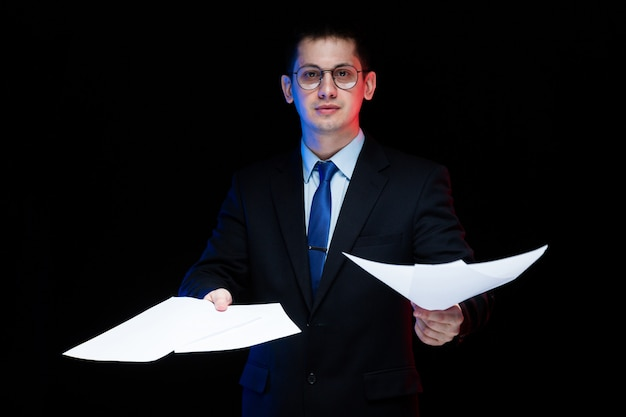 Portrait of confident handsome stylish businessman holding papers in his hands  black