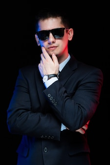 Portrait of confident handsome stylish businessman in sunglasses touching his chin on black