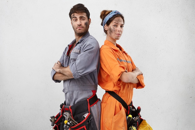 Portrait of confident handyman and his female colleague stand back to each other