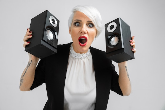 Portrait of a confident lady in a suit with speakers in her hands on a light