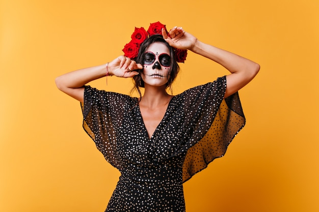 Portrait of confident latin woman with make-up for halloween posing  in her black dress