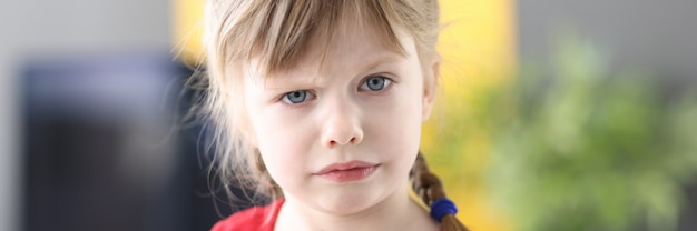 Portrait of confident little girl with blond hair looking at camera