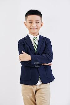 Portrait of confident little vietnamese schoolboy in formalwear folding arms