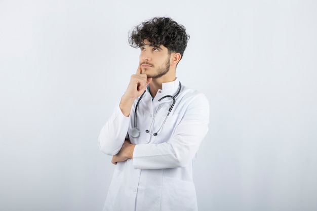 Portrait of a confident male doctor looking up isolated on white.