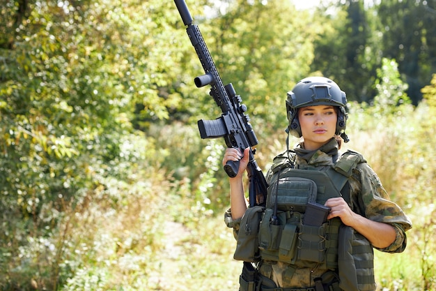 Portrait of confident military woman with a gun in forest