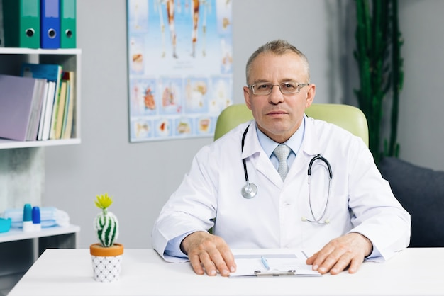 Portrait of confident old mature male head doctor physician in white medical uniform in glasses sitting at workplace