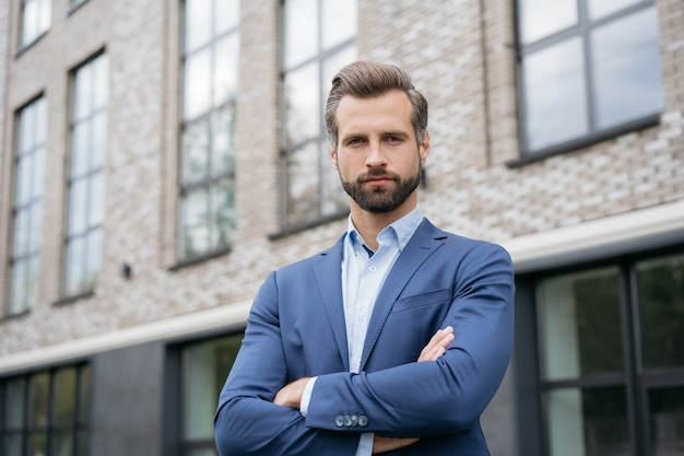 Portrait of confident real estate agent with arms crossed looking at camera successful business