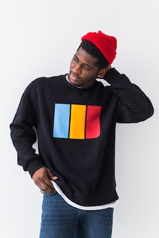 Portrait of confident sexy man in stylish sweatshirt on white wall