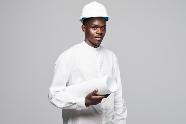 Portrait of confident, smiling afro american architect man with blueprint, looking at camera isolated on gray background