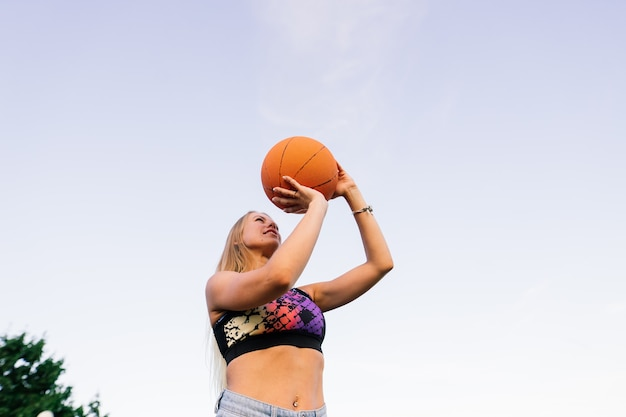 Portrait of confident smiling female basketball player with ball in hand and looking at a camera