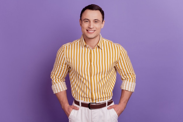Portrait of confident successful guy hands pockets toothy smile look camera on purple background