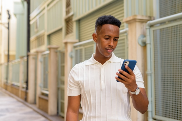 Portrait of confident young african businessman wearing casual clothes and using mobile phone