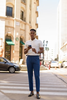 Portrait of confident young african businessman wearing casual clothes and using mobile phone Premium Photo