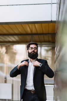 Portrait of confident young beard businessman adjusting her coat