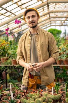 Portrait of confident young bearded greenhouse worker in casual shirt holding small shovel in orangery