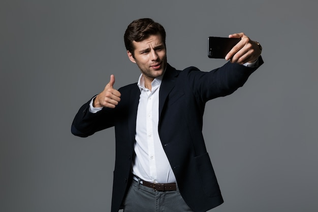 Portrait of a confident young businessman dressed in suit isolated over gray wall, taking a selfie