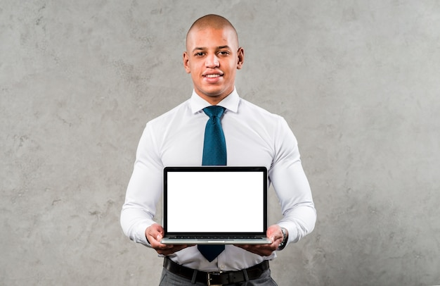 Portrait of a confident young businessman standing against grey wall showing laptop with white screen