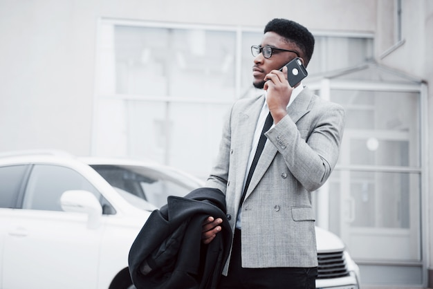 Portrait of a confident young businessman walking in the city talking on cell phone