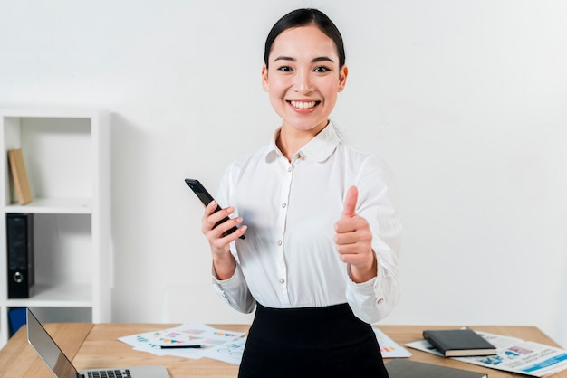 Portrait of a confident young businesswoman showing thumb up sign toward camera in the office