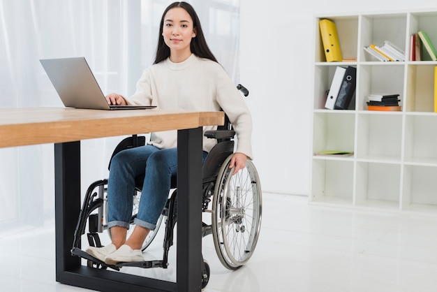 Portrait of a confident young businesswoman sitting on wheelchair using laptop in the office