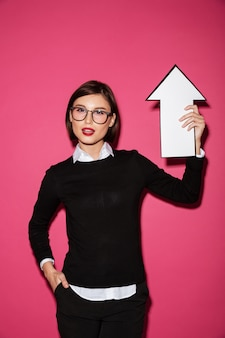 Portrait of a confident young businesswoman with arrow pointing up