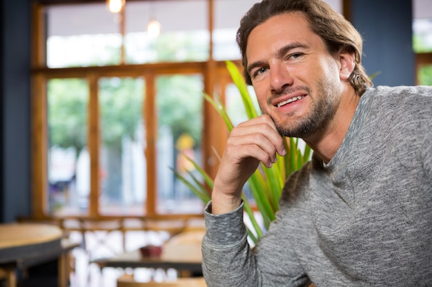 Portrait of confident young man in coffee shop