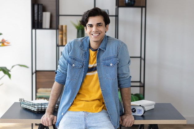 Portrait of confident young successful businessman in casual clothes at workplace. entrepreneur is standing at office