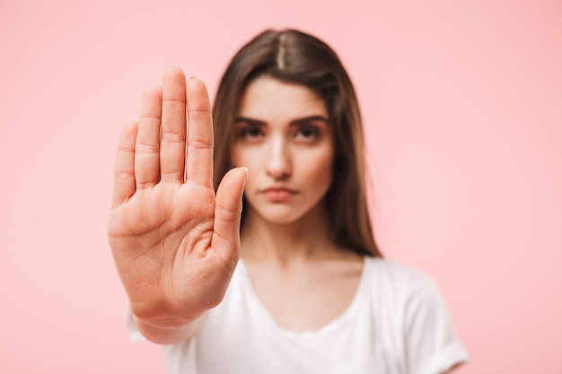 Portrait of a confident young woman showing stop