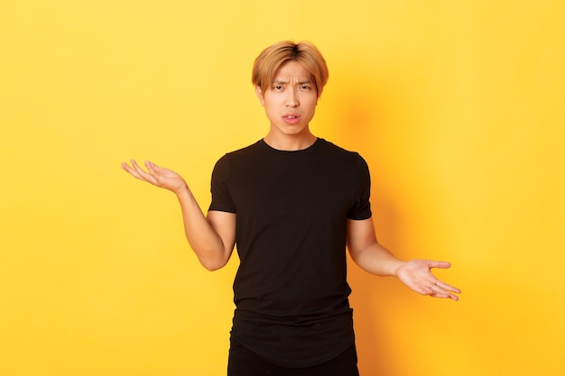 Portrait of confused and annoyed asian guy spread hands sideways, cant understand something, standing yellow wall