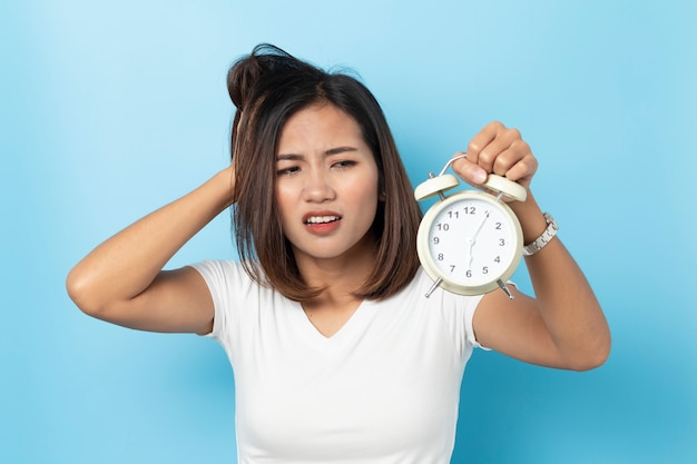 Portrait of confused asian young girl holding alarm clock isolated on blue