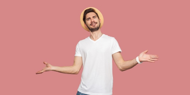 Portrait of confused bearded young man in white shirt with hat standing with raised arms and looking at camera with serious face. indoor studio shot, isolated on pink background copyspace.