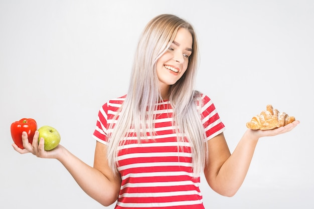 Portrait of a confused beautiful young blonde woman choosing between a healthy and unhealthy food. isolated over white background.