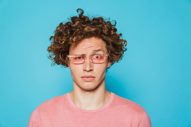 Portrait of a confused curly haired man looking at camera