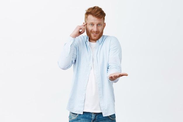 Ritratto di ragazzo caucasico bello rosso confuso e dispiaciuto che rotola il dito indice sulla tempia e indica con il palmo, comportandosi come un matto