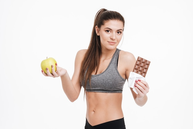 Portrait of a confused fitness woman holding chocolate in one hand and apple in the other, looking at front isolated