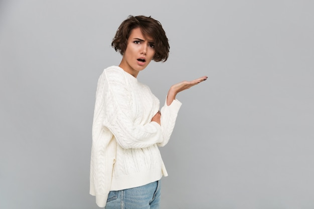 Portrait of a confused frustrated woman in sweater