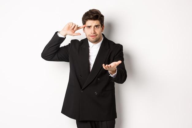 Ritratto di uomo d'affari bello confuso che rimprovera dipendente, indicando la testa e la macchina fotografica, in piedi deluso su sfondo bianco.