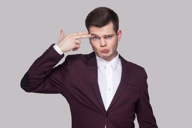 Portrait of confused handsome young man in violet suit and white shirt, standing, looking at camera with serious face and gun gesture. indoor studio shot, isolated on grey background.